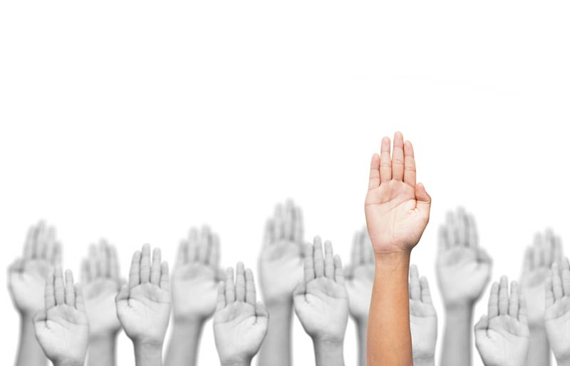 A close-up image of a group of raised hands in with one raised above the rest.