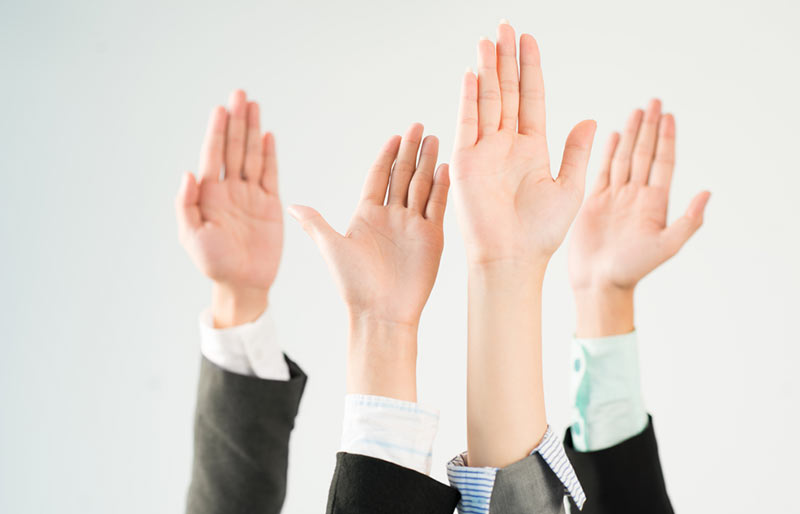 An image of four people wearing business shirts and suits raising their hand.
